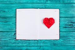 Hjärta av origami av rött papper Öppen anteckningsbok med rengöringsidor och en pappers- hjärta Röd hjärta och dagbok på en blå b Royaltyfri Bild