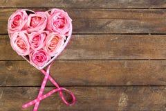 Hjärta av rosor i rosa färger med bandet på träbakgrund arkivfoton