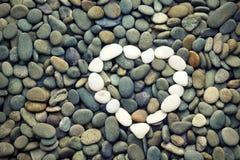 Hjärta av stenar på kiselstenar för ett bakgrundshav Arkivfoton