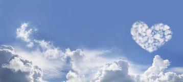 Hjärta för blå himmel och förälskelseformade fluffiga moln arkivbilder
