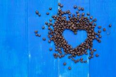 Hjärta för kaffebönor på träbräde Arkivfoton