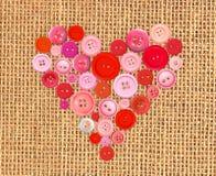 Hjärta för röda knappar på bakgrund för säckkanfassäckväv Royaltyfria Bilder