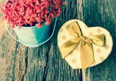Hjärta formad gåvaask med blomman. Arkivfoto