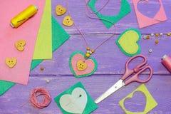 Hjärta formad hängehalsband Valentindaghalsband som göras av kulör filt, pärlor och en träknapp Hantverktillförsel Royaltyfri Fotografi