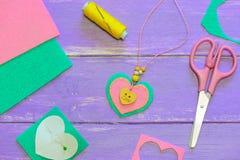 Hjärta formad hängehalsband Valentindaghalsband som göras av kulör filt, pärlor och en träknapp Hantverktillförsel Royaltyfria Foton
