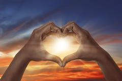 Hjärta formad hand med soluppgång arkivbild