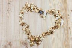 Hjärta-formad mysli och sädesslag på trätabellen royaltyfri fotografi