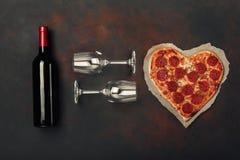 Hjärta formad pizza med mozzarellaen, sausagered, vinflaskan och vinglas två Kort för valentindaghälsning på rostig bakgrund fotografering för bildbyråer
