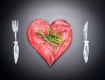 Hjärta formad rå kotlett av kött Köttförälskelse med målat bestick: gaffel och kniv Mörk svart tavlabakgrund royaltyfria bilder
