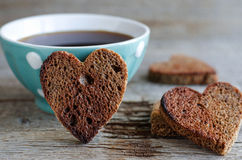 Hjärta formad rågrostade bröd och kopp kaffe Arkivbilder