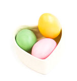 Hjärta formade asken mycket av färgrika påskägg på vit Arkivbild