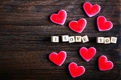 Hjärta formade att tugga godisar och ord som jag älskar dig på kuber, träbakgrund Fritt avstånd för din text arkivfoto