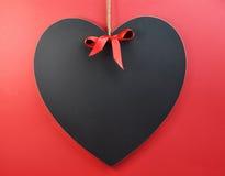 Hjärta formade blackboarden på en röd bakgrund med kopierar utrymme för din text här. Arkivbild