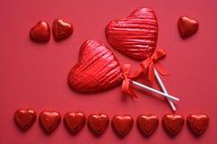 Hjärta formade choklader på röd bakgrund fotografering för bildbyråer