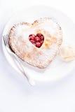 Hjärta formade den körsbärsröda pajen med vaniljglass på vit Arkivbild