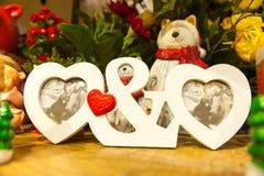 Hjärta formade fotoramen på den wood tabellen mot bakgrunden av julleksaker Arkivbilder