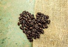 Hjärta formade kaffebönor på en säckväv plundrar Arkivbild