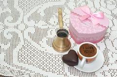 Hjärta formade kakan med den röda gåvaasken med pilbågen och koppen kaffe royaltyfria bilder