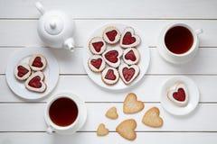 Hjärta formade kakor för valentindag med tekannan och två kopp te på vit träbakgrund Arkivfoton