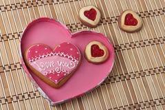 Hjärta-Formade kakor i en rosa färg boxas på ett trä vadderar. Royaltyfria Bilder