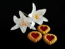 Hjärta-formade kakor och två vita liljor Arkivbilder