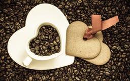 Hjärta formade koppen och kakan på bakgrund för kaffebönor arkivfoton