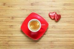 Hjärta formade sötsaker som slås in i en ljus röd folie som ligger på en trätextur med den röda koppen av coffe nära den Fotografering för Bildbyråer