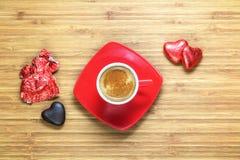 Hjärta formade sötsaker som slås in i en ljus röd folie som ligger på en trätextur med den röda koppen av coffe nära den Arkivbild