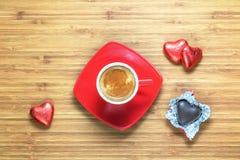 Hjärta formade sötsaker som slås in i en ljus röd folie som ligger på en trätextur med den röda koppen av coffe nära den Royaltyfri Fotografi