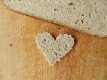 Hjärta formade stycket av bröd framme av fullt bröd Arkivbild