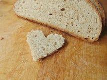 Hjärta formade stycket av bröd framme av fullt bröd Arkivbilder