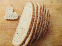 Hjärta formade stycket av bröd framme av fullt bröd Royaltyfria Bilder