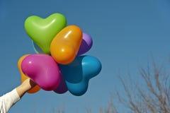 Hjärta formar ballonger rymmer vid en människa räcker Royaltyfri Foto