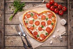 Hjärta format begrepp för förälskelse för pizzamargherita vegetariskt med mozzarellaen, tomater, persilja, kniven, gaffeln och vi arkivbilder