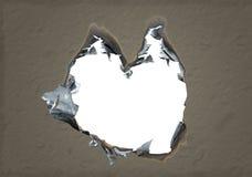 Hjärta format bränt hål i papper. Arkivbild