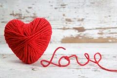 Hjärta-format garnnystan, med ord av förälskelse Arkivfoton