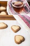 Hjärta-format kakor och te för dag för St-valentin` s Arkivbilder