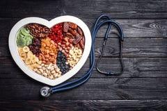 Hjärta format magasin med muttrar och torkade frukter nära stetoskopet på träbakgrund royaltyfri foto