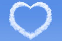 Hjärta format moln i blå himmel Arkivbilder