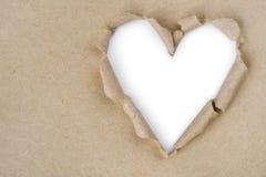 Hjärta format sönderrivet till och med återanvänt papper royaltyfri foto