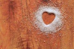 Hjärta-format socker på skärbräda arkivbild
