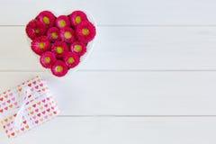 Hjärta från den röda bellis- och gåvaasken med pilbågen på träbakgrund i vit fotografering för bildbyråer