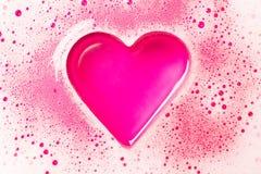 Hjärta från ett skum på en rosa bakgrund arkivbild