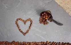 Hjärta från kaffebönor med säckväv och skeden på grå kökworktopbakgrund arkivfoto