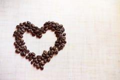 Hjärta från kaffebönor på träbakgrund placera text royaltyfri fotografi