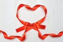 Hjärta från rött band på vit träbakgrund drinking glass straws valentindagbakgrund för födelsedagen, ferie royaltyfri foto