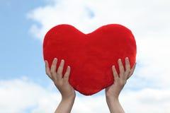 Hjärta i händer mot himmel Arkivfoton