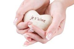 Hjärta i handen som isoleras med franska ord för älskar jag, dig. Fotografering för Bildbyråer