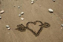 Hjärta i sanden med en pil Arkivfoton