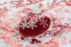Hjärta med vita snöflingor svävar i vatten valentin för dag s Arkivbilder